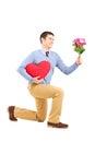 Uśmiechnięty męski klęczenie z kwiatami i czerwonym sercem Fotografia Stock