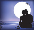 Uddling couple on a moonlit beach silhouette of cuddling Royalty Free Stock Image