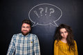Ugly couple grimacing over chalkboard background young joking and Royalty Free Stock Images