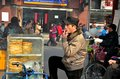 Uighur street side bread vendor smokes shanghai china february a man rests his leg on his bicycle vending vehicle laden with Stock Photo