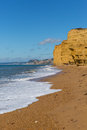UK Jurassic coast Burton Bradstock beach Dorset with sandstone cliffs and white waves in summer with blue sea and sky Royalty Free Stock Photo