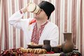Ukrainian cossack in national clothes is sitting at the table and eats Royalty Free Stock Photos