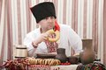 Ukrainian cossack in national clothes is sitting at the table and eats Royalty Free Stock Image