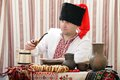 Ukrainian cossack in national clothes smokes a pipe with tobacco Royalty Free Stock Photography