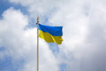 Ukrainian flag on a flagpole in the wind develops in the background of the sky Royalty Free Stock Photo