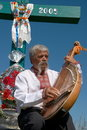 Ukrainian musician with bandura under cross 2 Stock Photography