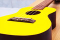 Ukulele close up a of a yellow on clean table Royalty Free Stock Image
