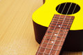 Ukulele close up a of a yellow on clean table Royalty Free Stock Images