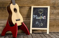 Ukulele guitar and blackboard with the word Music written on wooden background