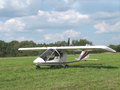 Ultralight aircraft in grassy field on the ground a with trees and blue sky with clouds the background Stock Photo