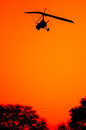 Ultralite aircraft as sihouette an comes in for a landing the sun is setting revealing only a black sihoutte of the and the tips Royalty Free Stock Photos