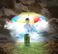 Umbrella boy with rays of sunshine and hope a young child is holding a rainbow glowing out the is surrounded a dried up landscape Royalty Free Stock Image