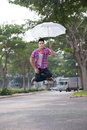 Umbrella levitation boy sitting in the air with an Stock Photo