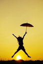 Umbrella woman jump and sunset silhouette Stock Photos