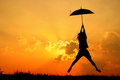 Umbrella woman jump and sunset silhouette Royalty Free Stock Photo