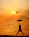 Umbrella woman jump and sunset silhouette in Lake Stock Photo