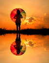 Umbrella woman and sunset silhouette,Water reflect Royalty Free Stock Photography
