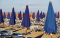 Umbrellas blue and orange in a sun drenched sea beach closed Stock Images