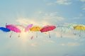 Umbrellas line up across the sky conceptual photo of different color lined sun is behind them shining and this concept can Royalty Free Stock Photography