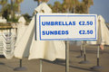 Umbrellas sunbeds hire beach Stock Image