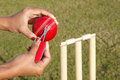 Umpire cutting the ripped thread of a cricket ball Royalty Free Stock Image
