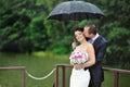 Un couple excited de mariage en jour pluvieux Photographie stock libre de droits