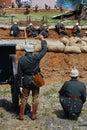 Un soldato reenactor del tedesco dà un comando sparare da un cannone Fotografia Stock