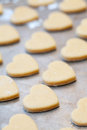 Unbaked heart shaped shortbread cookies on baking tray selectiv rows of selective focus Stock Photos