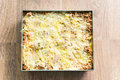 Unbaked lasagne in oven dish on wooden background Royalty Free Stock Photo