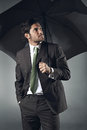Uncertain businessman with umbrella looks up worried expression Royalty Free Stock Image