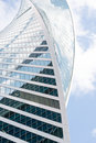 Uncommon high rise building on blue sky background with cloud reflection close up view Royalty Free Stock Photos
