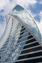 Uncommon skyscraper on blue sky with clouds background cloud reflection close up view Royalty Free Stock Image