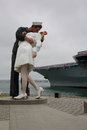 Unconditional Surrender statue with USS Midway