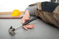 Unconscious worker lying on the floor with hammer in the hand Stock Images