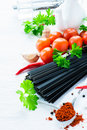 Uncooked black pasta with tomatoes herbs spices fresh and oil jug selective focus Royalty Free Stock Photo