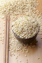 Uncooked brown rice in a bowel and chopsticks with woody background Royalty Free Stock Images