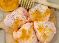 Uncooked chicken thighs raw sprinkled with curry spices on a wooden board Stock Images
