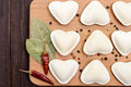 Uncooked dough in the shape of a heart dumplings, ravioli, pelmeni, on a cutting board.