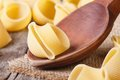 Uncooked italian macaroni lumaconi on wooden spoon closeup horizontal Stock Photography