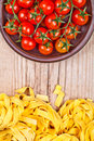 Uncooked pasta and fresh tomatoes on rustic wooden background Royalty Free Stock Photo