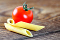 Uncooked penne pasta and cherry tomato Stock Photography