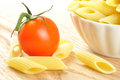 Uncooked penne pasta and a cherry tomato, closeup Stock Photography