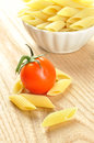 Uncooked penne pasta and a cherry tomato, closeup Stock Photo