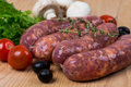 Uncooked raw sausages on wooden board with lettuce tomatoes mushrooms Royalty Free Stock Photos