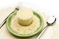 Uncooked rice in green plate with spoon and fork Royalty Free Stock Photos