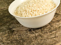 Uncooked rice some risotto in a white bowl on a wooden background Royalty Free Stock Photos