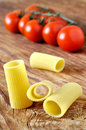 Uncooked rigatoni pasta and cherry tomatoes Stock Photo