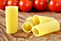 Uncooked rigatoni pasta and cherry tomatoes Royalty Free Stock Photos