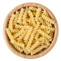 Uncooked rotini pasta in wooden bowl isolated on white background Royalty Free Stock Photo
