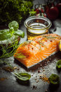 Uncooked salmon fillet with fresh herbs and spices basil dill olive oil on a kitchen counter ready to cook a gourmet seafood Royalty Free Stock Photos